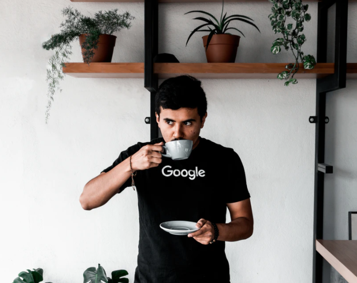 man in google t-shirt sipping a drink